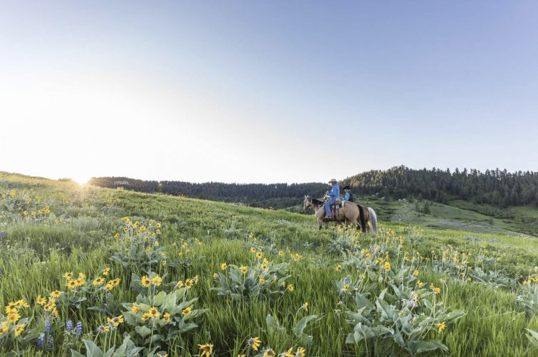 Two cowboys on horseback riding through Horsethief Basin Ranch.