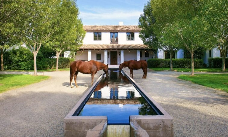 Two horses drinking from trough at luxury ranch in Rancho Santa Fe, California.