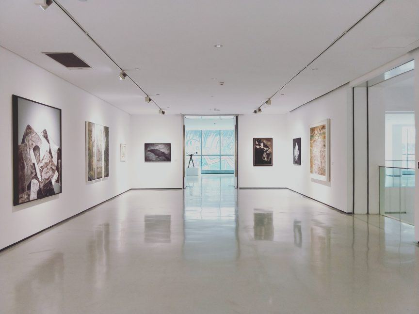 Artwork hanging on white walls of chic museum where real estate agents can meet luxury clients