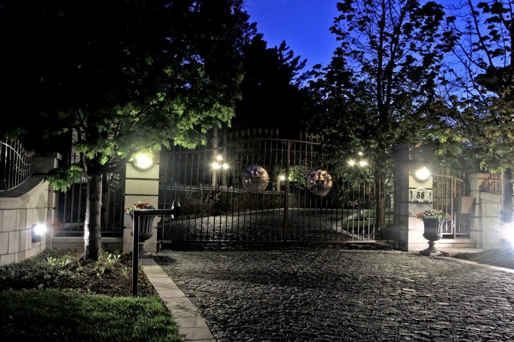 stone pathway and iron gate leading to a luxury home at night