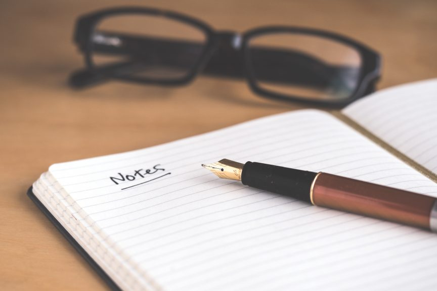 glasses and notebook for notes and continuing education for luxury real estate agents to real estate success
