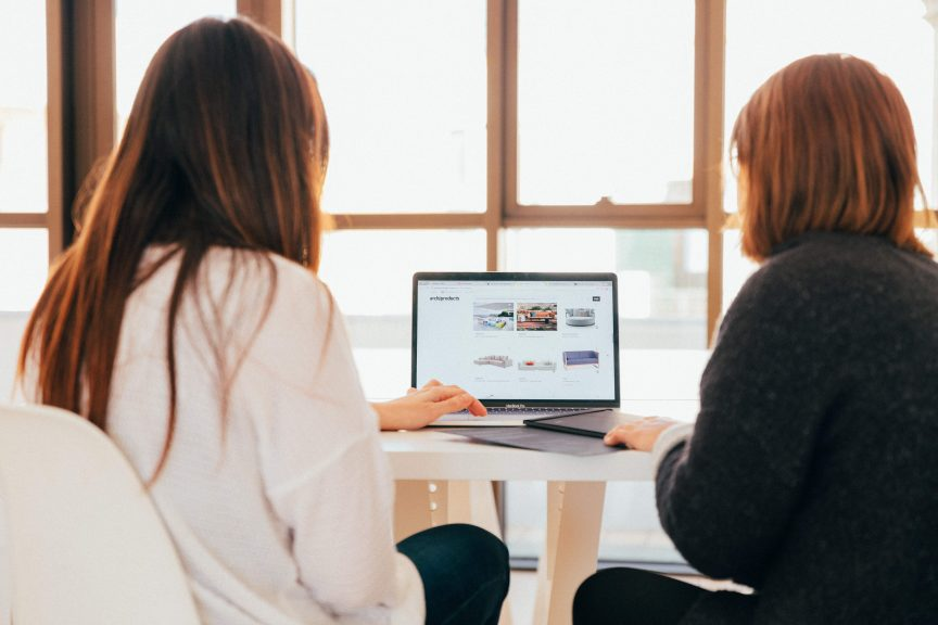 two ladies looking at laptop together to read about mastering relationships for real estate success