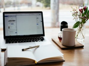 luxury realtor's desk with a laptop, notebook, and coffee mug – a brainstorm on content that brings real estate success