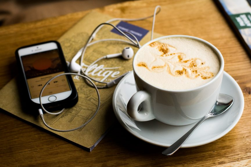 a wood table with a cappuccino and phone with headphones plugged in, playing Estate of Mind, a podcast for luxury real estate success