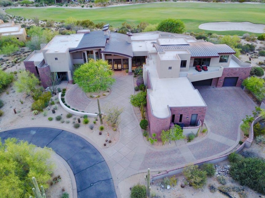 A overhead shot of a luxury home sitting on a golf course to start a virtual home tour for real estate success