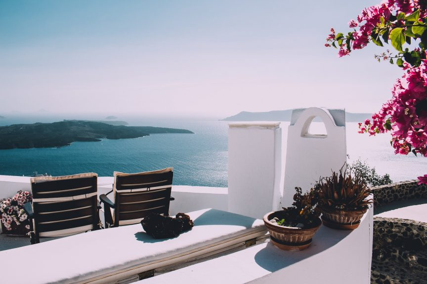 white patio with fushia colored plant and 2 wooden chairs by the sea
