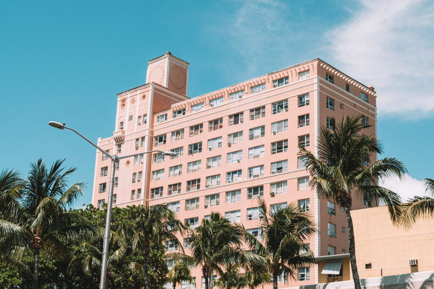 A luxury building with palm trees in front