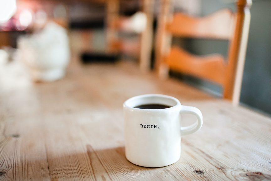 A mug filled with coffee with the word begin printed on it
