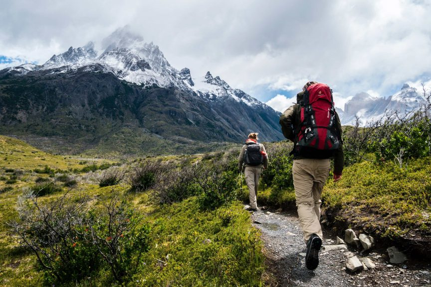 A couple hiking towards a snow capped mountain