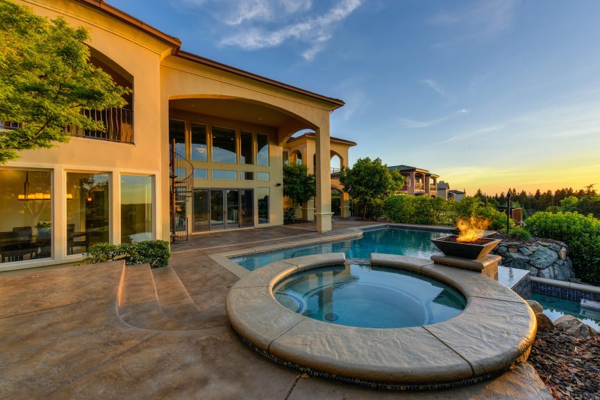 A pool, jacuzzi, and fire pit in the backyard of a luxury home