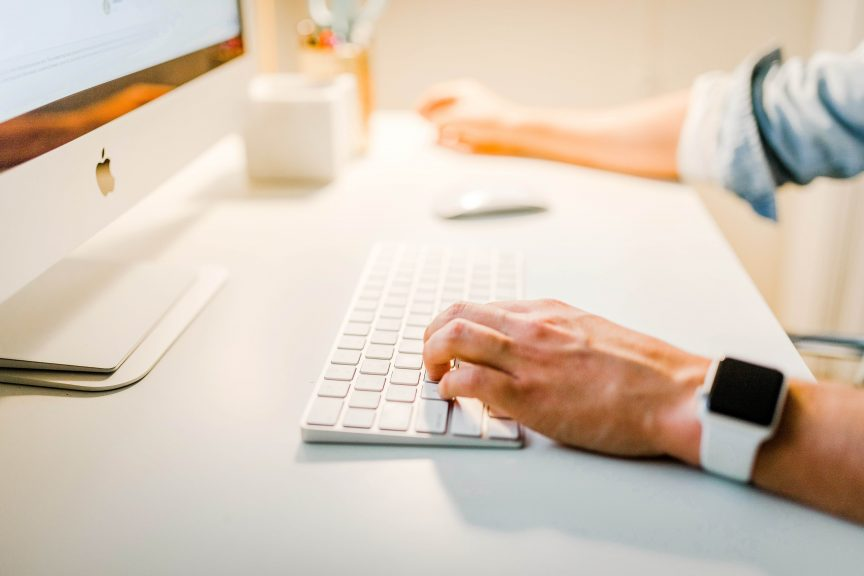 A man's hand typing on his computer keyboard