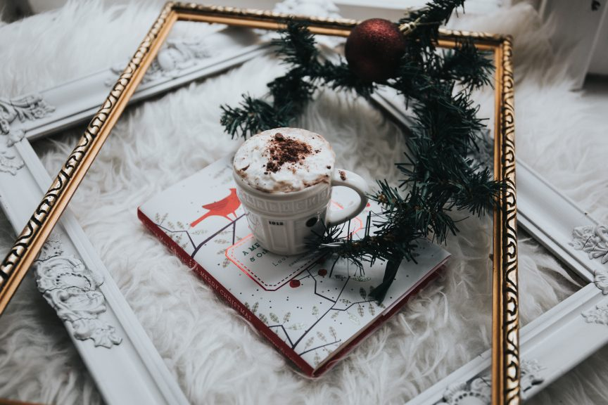 A cup of specialty coffee in the middle of a holiday decorated frame