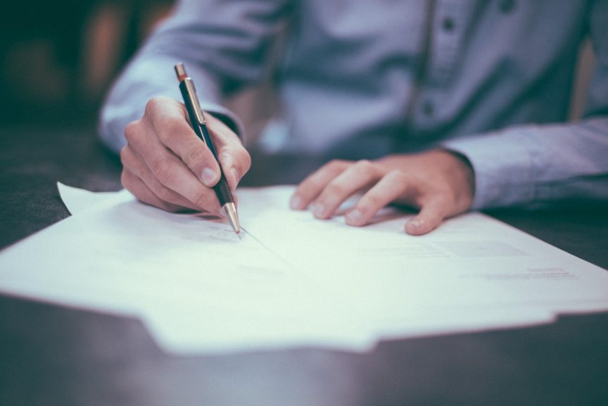 A person signing paperwork while sitting at a table