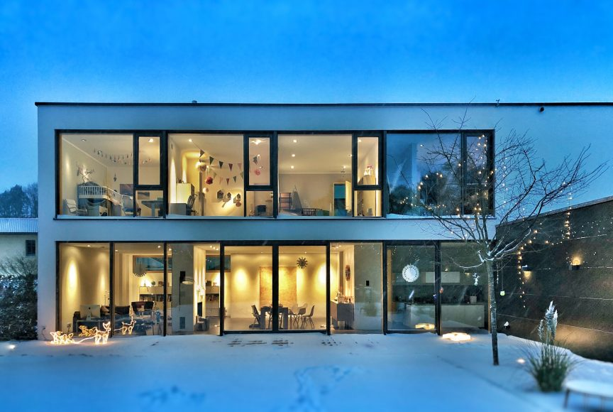 An exterior shot taken at dusk of a luxury home with many windows overlooking a snowy backyard