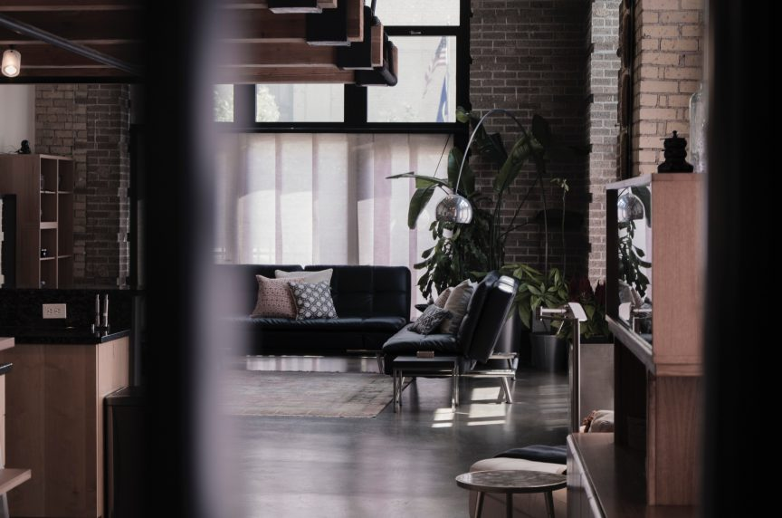 an open living room space featuring brick walls, dark flooring, and natural wood furniture