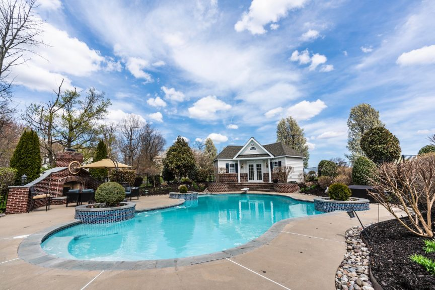 a luxury home's backyard featuring a large swimming pool on a sunny day