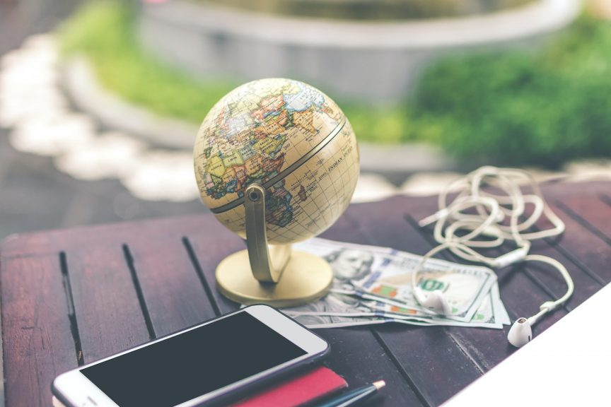 a table-top globe of the world next to a cell phone, paper currency, and headphones all on top of a wooden outdoor table