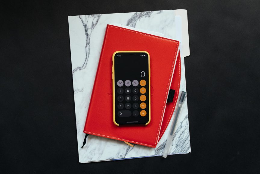 a mobile phone with the calculator app open on screen, resting on top of a red daily planner and a file folder with a marble pattern