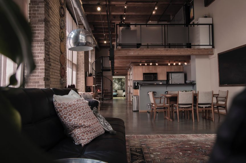 a luxury living room space decorated in wood tones and brick, that opens up into a kitchen with stainless steel appliances and featuring an office loft accessed via a dark iron spiral staircase