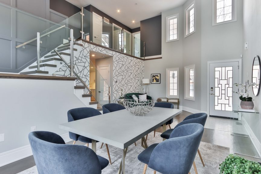 entryway area of a luxury home space that opens up into a modern-style dining area that can be seen from a second-floor open hallway space