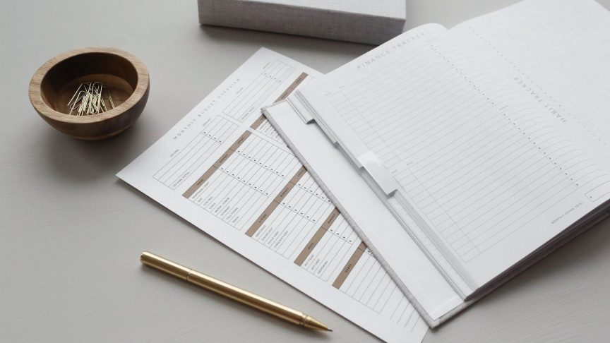 a monthly budget overview sheet and finance tracker and gold pen
