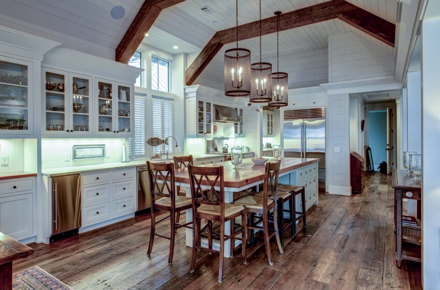 a large kitchen with a beamed ceiling, brass accessories throughout, and a large island with a butcher block top and ample seating and storage space