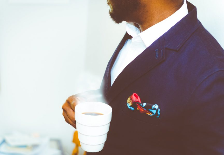 a man wearing a navy sports coat while drinking hot coffee from a white mug