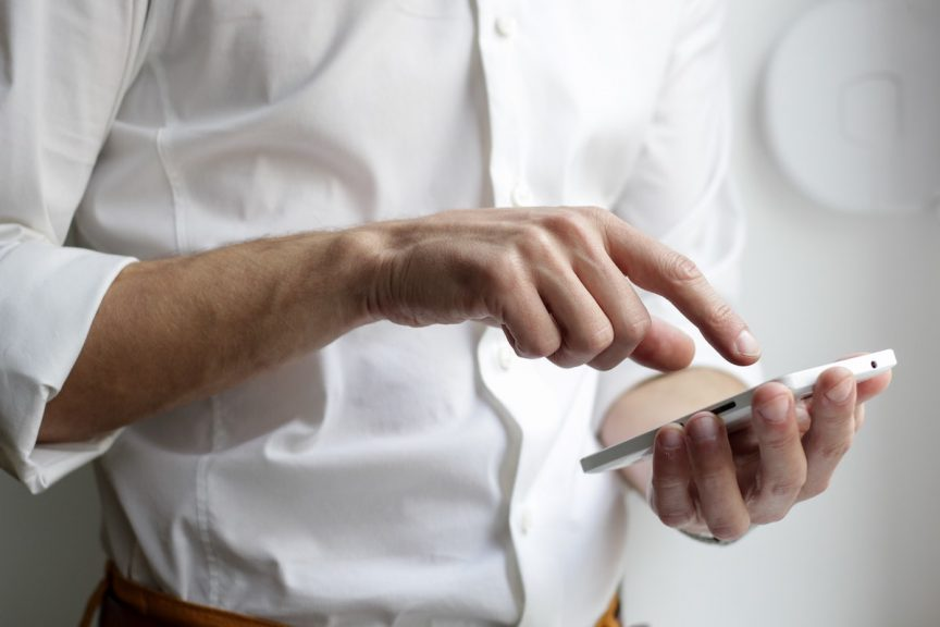 a man wearing a white, buttoned-down shirt with his sleeves rolled up who is using his mobile phone device