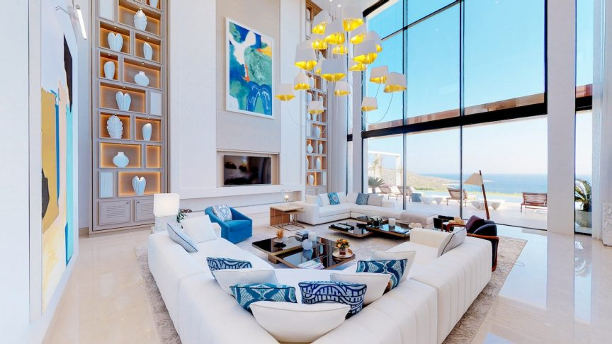 a large living room decorated in light, beach tones with cathedral ceilings, two large couches, and floor-to-ceiling windows overlooking the coast