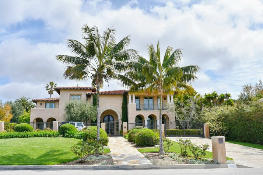 the exterior of a large, two-story, Spanish-style home with palm trees growing in the front yard