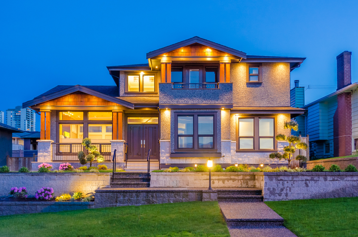 a large, two-story home lit up at night with exterior lighting