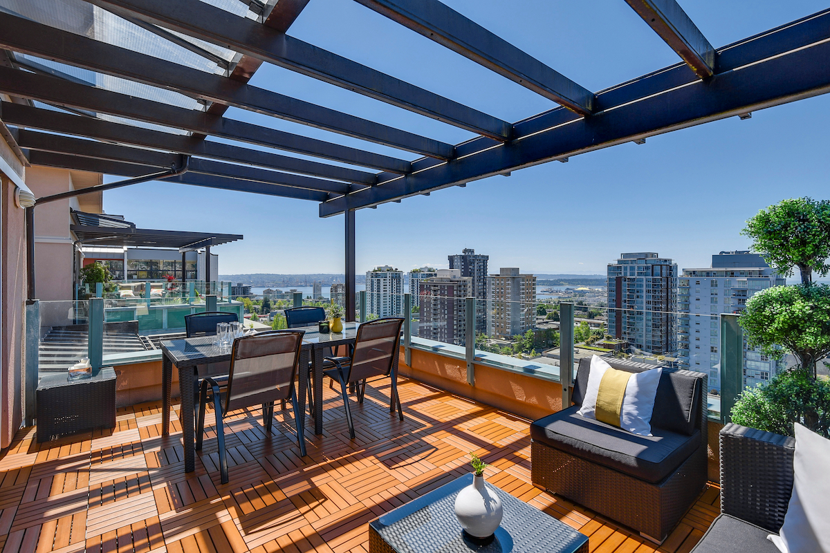 an outdoor balcony constructed and decorated in wood tones overlooking a city