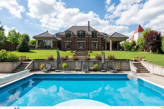 Large outdoor pool and historic luxury building.