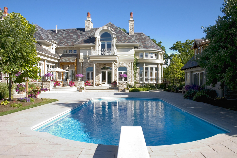 a large luxury home featuring a swimming pool in the backyard